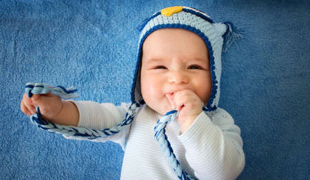 four month old baby in owl hat on a towel 版權商用圖片