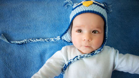 four month: four month old baby in owl hat on a towel Stock Photo