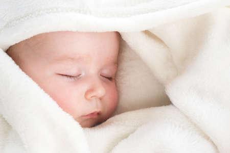 kleine jongen slapen op zachte witte deken