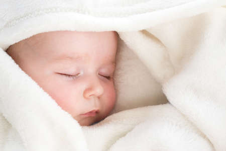 little boy sleeping on soft white blanket