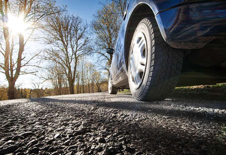 car tire: Car on asphalt road in spring morning Stock Photo