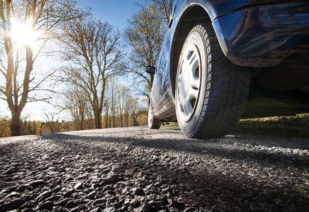 huellas de neumaticos: Coche en la carretera de asfalto en la mañana de primavera Foto de archivo