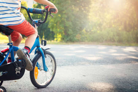 kinderschoenen: kind op een fiets bij asfaltweg Stockfoto