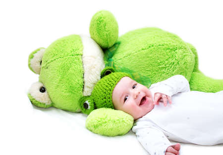 soft toy: baby in frog hat and soft toy Stock Photo