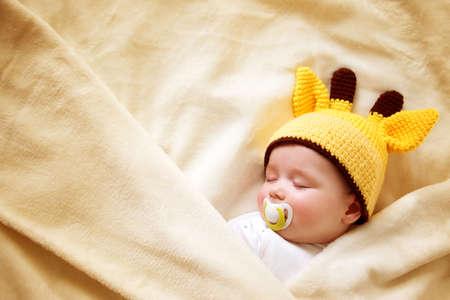 little boy sleeping on soft cream blanket