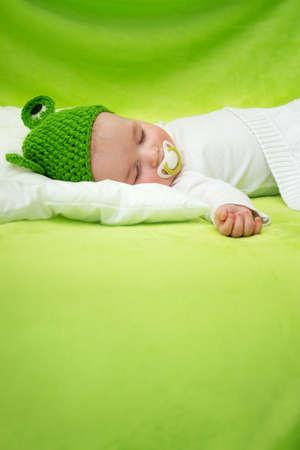 little boy lying on soft green blanket