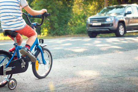 danger: niño en una bicicleta en la carretera de asfalto Foto de archivo