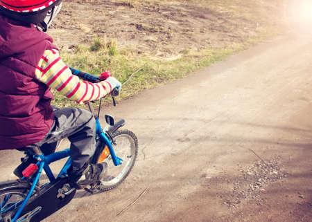 niños sanos: Muchacho en la bici en el camino de ripio en primavera Foto de archivo