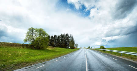 open country: wet road panorama with beautiful clouds in the sky
