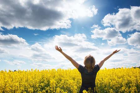 黄色の花を持つフィールドで若い女性