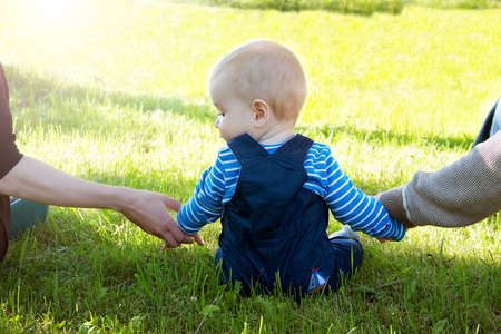 holding back: Baby with mother and father holding hands on the nature Stock Photo