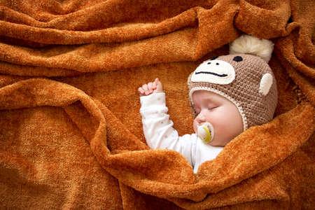 newborn animal: little baby in knitted montey hat on brown blanket