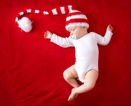 little baby in knitted red whitey hat on red blanket 스톡 콘텐츠