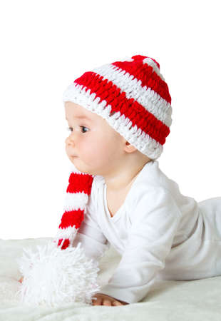 funny people: little baby in knitted red whitey hat on red blanket Stock Photo