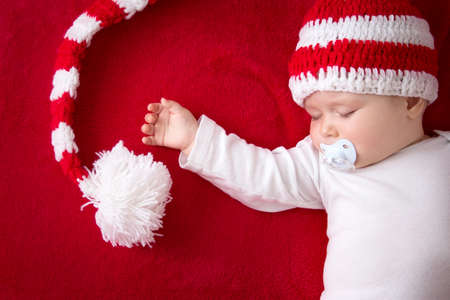 new baby: little baby in knitted red whitey hat on red blanket Stock Photo