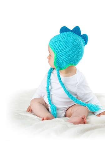 cute dinosaur: little baby in knitted dinosaur hat on soft blanket