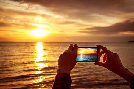 Manos de la mujer que sostienen el teléfono móvil en la puesta del sol Foto de archivo - 43586956
