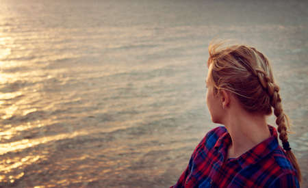 wonder: young blond woman looking at setting sun Stock Photo