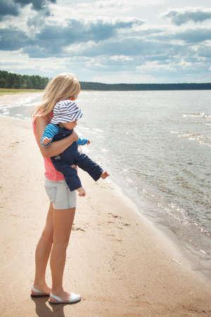 mama e hijo: mujer joven y el bebé en la playa cerca del mar Foto de archivo
