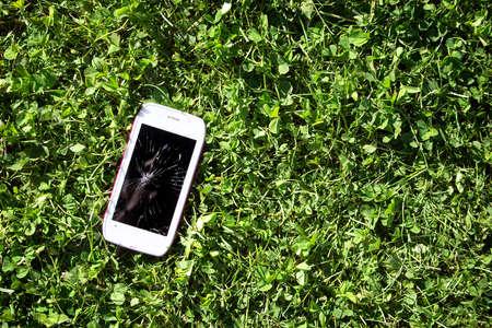 壊れた画面の緑の草の上に横たわるとスマート フォン 写真素材
