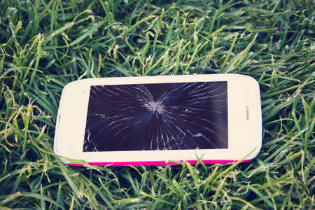 portable failure: Smartphone with broken screen lying on green grass