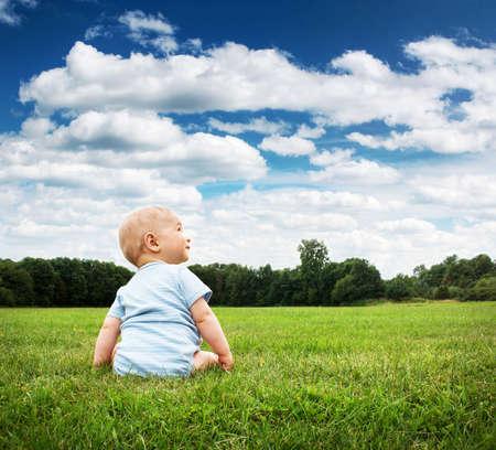 풀밭에 앉아 작은 아기 소년
