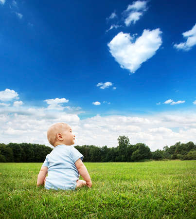 cloud shape: Little baby boy sitting on the grass Stock Photo