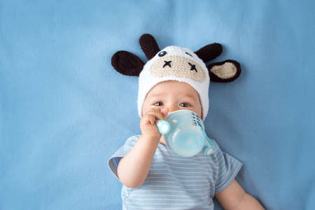 cute baby in a cow hat drinking milk