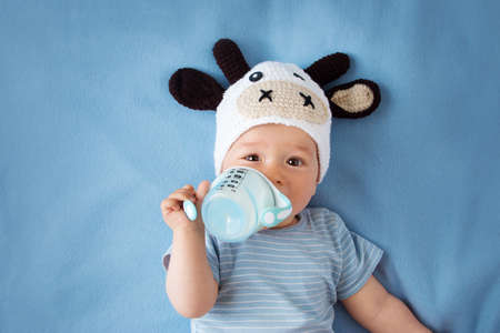 energy drink: cute baby in a cow hat drinking milk