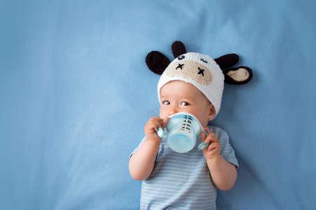 schattige baby in een koe hoed drinken melk