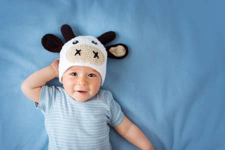 cute baby in a cow hat on blue blanket. Stock Photo