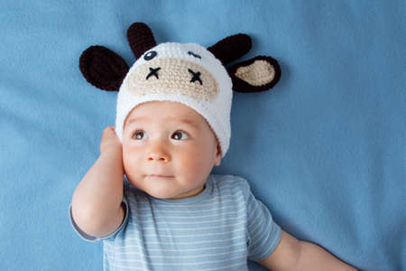 baby s: schattige baby in een koe hoed op blauwe deken Stockfoto