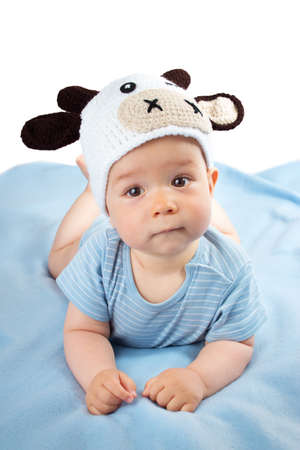 blue blanket: cute baby in a cow hat on blue blanket
