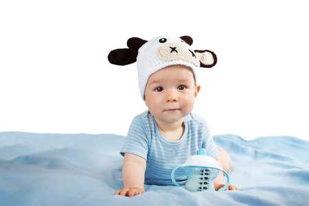 niedliches Baby in einem Kuh-Hut Trinkmilch