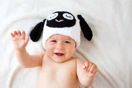 niedliches Baby in einem Schaf-Hut auf weiche Decke liegend