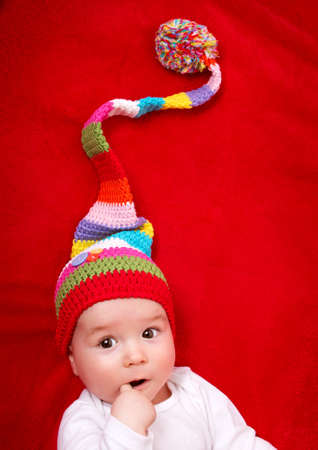 christmas hat: Baby in red and white hat on the bed Stock Photo