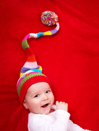 beautiful little boys: Baby in red and white hat on the bed Stock Photo