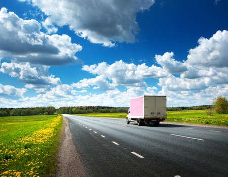 ciężarówka: droga asfaltowa na polu mniszka z małą ciężarówką Zdjęcie Seryjne