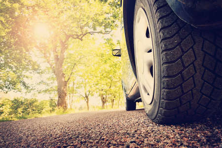 huellas de llantas: Coche en el camino de asfalto en día de verano en el parque Foto de archivo