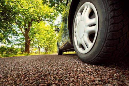 summer tire: Car on asphalt road on summer day at park
