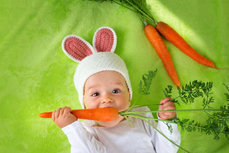 Baby in rabbit hat eating fresh carrot