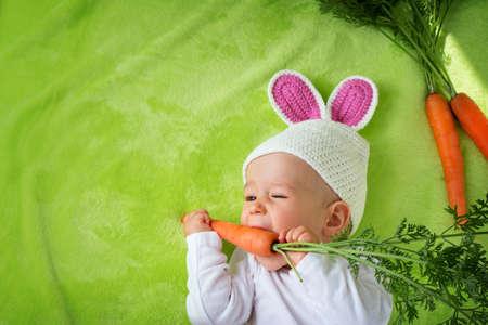 Baby in rabbit hat eating fresh carrot