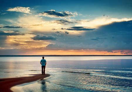 황혼의 바다에서 한 남자가 stamding 스톡 콘텐츠