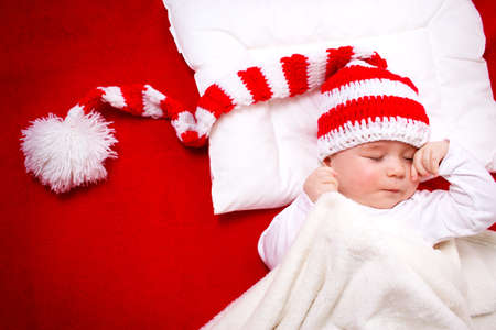 new baby: Sleepy baby on red blanket in knitted hat
