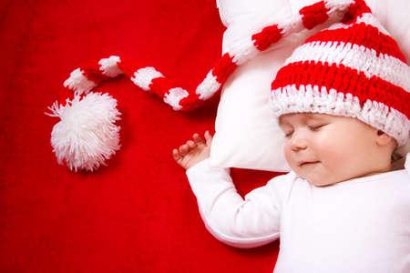 bebisar: Sömnig bebis på röd filt i stickad mössa Stockfoto