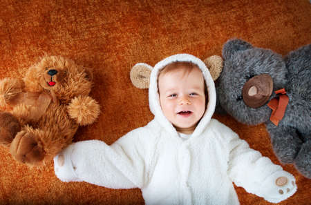 plush toys: 11 months baby in bear costume with plush toys Stock Photo