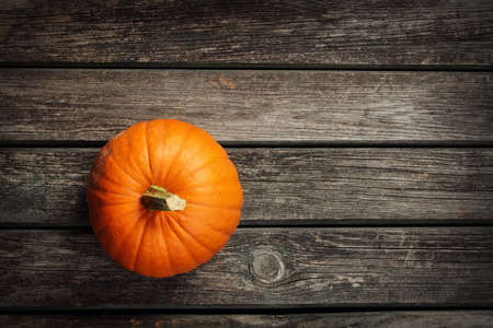 autumn colour: yellow pumpkin on old weathered wooden background