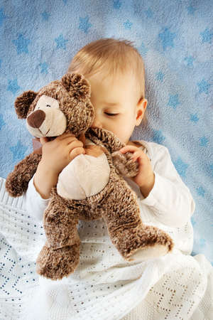 teddy bear love: One year old baby lying in bed holding a plush teddy bear Stock Photo