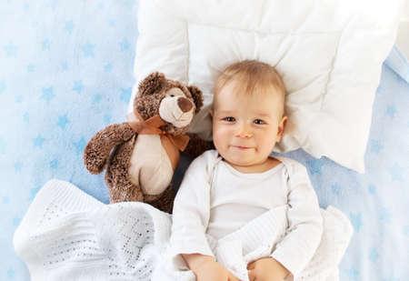 Een jaar oude baby liggend in bed met een pluche teddybeer