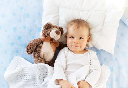 One year old baby lying in bed with a plush teddy bear Archivio Fotografico